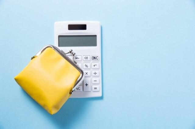 電卓とがま口の黄色い財布
